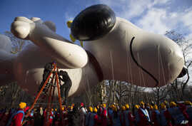 Workers prepare the giant Snoopy balloon before the 87th Annual Macy's Thanksgiving Day Parade, New York, Nov. 28, 2013.