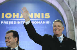 Romanian President Klaus Iohannis, right, waves next to Romanian prime minister Ludovic Orban, after exit polls were published, in Bucharest, Romania, Nov. 24, 2019.