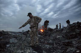 FILE - People walk amongst the debris at the crash site of a Malaysia Airlines flight MH17 near the village of Grabove, Ukraine, July 17, 2014.