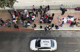 In this Nov. 10, 2019, photo, migrants gather at the U.S.-Mexico border in Tijuana, Mexico, to hear names called from a waiting…