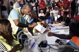 An electoral worker sorts ballots during the counting of votes for Guinea-Bissau's presidential runoff on December 29, 2019, in…