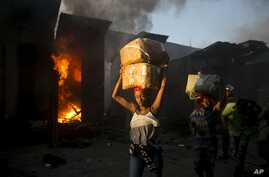 Vendors carry salvaged merchandise from the burned ruins of the Guerite Market that was engulfed in flames in Port-au-Prince, Haiti,vJan. 14, 2020.