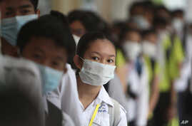 Students line up to sanitize their hands to avoid the contact of coronavirus before their morning class in Cambodia