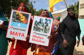 """Somali women chant slogans and hold placards written in Somali """"No more Explosions"""" and """"Silly criminal is Dangerous"""" as they…"""