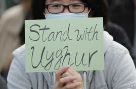 A man holds a sign during a rally to show support for Uighurs and their fight for human rights in Hong Kongy, Dec. 22, 2019.