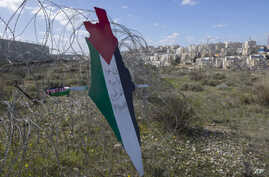 "Protesters post a placard with the colors of the Palestinian flags and Arabic that reads ""Jerusalem is the eternal capital of Palestine,"" at a barbed wire surrounding the Israeli separation wall and an Israeli settlement near Ramallah, Jan. 31, 2020."