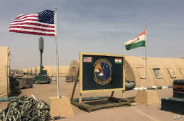 FILE - U.S. and Niger flags flutter side by side at a base camp supporting the construction of Niger Air Base 201 in Agadez, Niger, April 16, 2018.