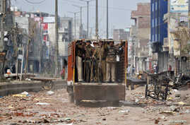 Policemen move in a truck in a riot affected area after clashes erupted between people demonstrating for and against a new citizenship law in New Delhi, India, Feb. 26, 2020.