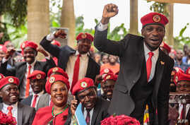 Singer turned politician Robert Kyagulanyi, also known as Bobi Wine gestures during a press conference, held at his home in…