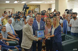 Ekrem Imamoglu (2L), the new Mayor of Istanbul from Turkey's main opposition opposition Republican People's Party (CHP) poses with a gift from Istanbul for the removed mayor of Diyarbakir, Adnan Selcuk Mizrakli, Aug. 31, 2019.
