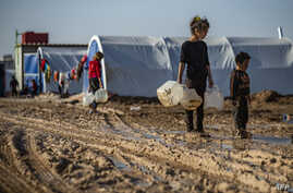 Syrian children carry jugs to fill with water in Washukanni camp, on December 16, 2019, which was recently established on the…