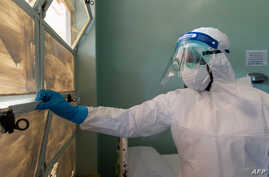 A medical staff member wears protective equipment while closing a window at the Wilkins Infectious Diseases Hospital in Harare…
