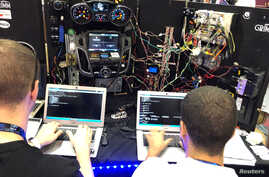 FILE - Attendees of the 2019 DEF CON cybersecurity event are seen at the conference's car hacking village in Las Vegas, Nevada