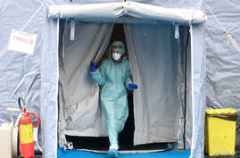 A medical worker wearing protective mask is seen at a medical checkpoint at the entrance of the Spedali Civili hospital