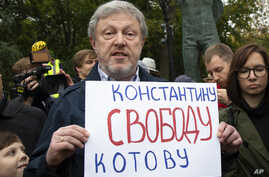 """Russian politician Grigory Yavlinsky holds a poster reading: """"Freedom to Konstantin Kotov"""", an opposition activist in jail, during a protest in the center of Moscow, Russia, Aug. 17, 2019."""