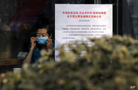 """A woman puts on a mask near a notice board that reads """"Bans on wild animals trading following the coronavirus outbreak"""" at a cafe in Beijing, Monday, Feb. 10, 2020."""