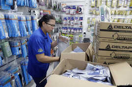 A medical supply store worker organizes masks that customers are buying as a precaution against the spread of the new coronavirus COVID-19, in Sao Paulo, Brazil, Feb. 26, 2020.