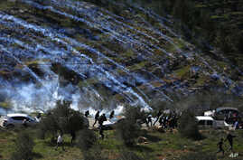FILE - Palestinian demonstrators run away from tear gas fired by Israeli forces during a protest against Israeli settlements and U.S. President Donald Trump's Mideast initiative, in the West Bank village of Beita near Nablus, Feb. 28, 2020.