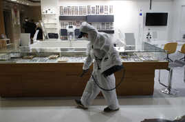 A worker wearing protective gear sprays disinfectant as a precaution against the new coronavirus in an eyeglass shop at a…