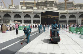 Workers clean the Grand Mosque, during the minor pilgrimage, known as Umrah, in the Muslim holy city of Mecca, Saudi Arabia, Monday, March 2, 2020.