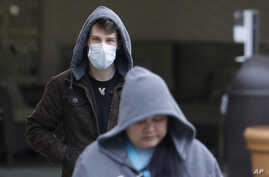 A man wearing a mask walks away from the entrance of the Life Care Center in Kirkland, Wash., near Seattle