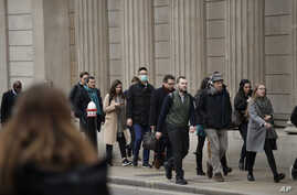 A man wearing a face mask walks past the Bank of England in London, March 4, 2020.