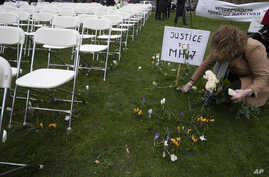 A woman places a rose next to 298 empty chairs, each chair for one of the 298 victims of the downed Malaysia Air flight MH17, in a park opposite the Russian embassy in The Hague, Netherlands, March 8, 2020.