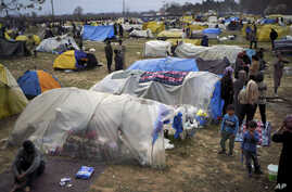 Migrants stand by tends in a camp set up near the Turkish-Greek border in Pazarkule, Edirne region, Turkey, Tuesday, March 10,…