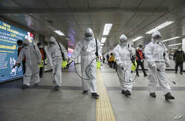 Workers wearing protective gears disinfect as a precaution against the new coronavirus at the subway station in Seoul.