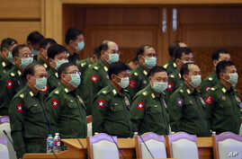 Military representatives stand upon arrival of Parliament Chairman T Khun Myat during a regular session of the Union Parliament Wednesday, March. 11, 2020, in Naypyitaw, Myanmar.