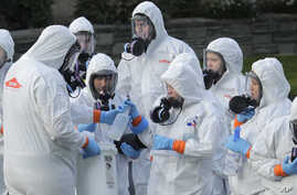 Workers from a Servpro disaster recovery team wearing protective suits and respirators are given supplies as they line up…