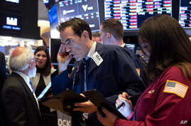 Trader Gregory Rowe, center, and others work on the floor of the New York Stock Exchange, March 16, 2020.