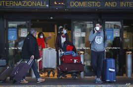 People walk upon arrival at the Malpensa airport of Milan, Italy, March 22, 2020.