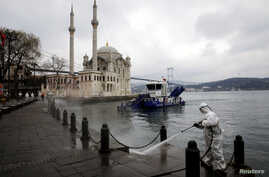 A worker sprays disinfectant outside Ortakoy Mosque, to prevent the spread of coronavirus disease (COVID-19), in Istanbul,…