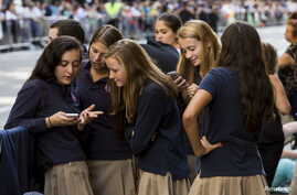 A group of Catholic school girls look at their phones as they wait on the route that Pope Francis will take later in the day…