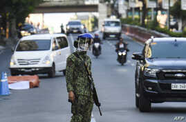 A policeman wearing a face mask stands guard at a checkpoint in Manila, Philippines, March 25, 2020, after the government imposed an enhanced quarantine as a preventive measure against the spread of the coronavirus.