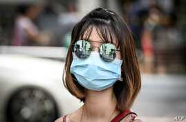 FILE - A woman wearing sunglasses and a mask to protect against the coronavirus walks on a street in Bangkok, Thailand, Feb. 13, 2020.