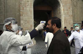 An Afghan health worker, left, takes the temperature of a guest to check for coronavirus at the entry gate of presidential palace during in an inauguration ceremony for President Ashraf Ghani in Kabul, Afghanistan, March 9, 2020.