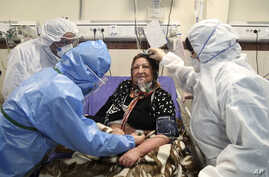 Medics treat a patient infected with the new coronavirus, at a hospital in Tehran, Iran, March 8, 2020.