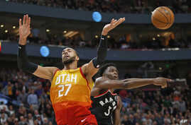 Toronto Raptors forward OG Anunoby (3) knocks the ball from Utah Jazz center Rudy Gobert (27) as he drives to the basket in the second half during an NBA basketball game, March 9, 2020, in Salt Lake City.