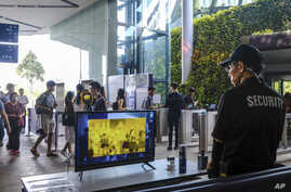 A security officer views a thermal screening monitor as visitors enter Gardens by the Bay nature park, in Singapore, March 14, 2020.