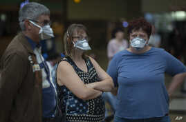 People wearing masks wait for passengers at Johannesburg's O.R. Tambo International Airport, South Africa, March 16, 2020, a day after President Cyril Ramaphosa declared a national state of disaster.