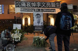 FILE - People attend a vigil for Chinese doctor Li Wenliang, in Hong Kong, Feb. 7, 2020. Li, who got in trouble with authorities for sounding an early warning about the coronavirus outbreak, died Feb. 7, 2020, after being infected.