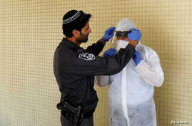 An Israeli police officer helps a Health Ministry inspector put on protective gear before they go up to the apartment of a person in self-quarantine as a precaution against the coronavirus spread, in Hadera, Israel, March 16, 2020.