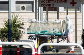 A medical worker in a protective suit stands with an isolation stretcher in front of the Columbus Clinic, where patients suffering from coronavirus disease (COVID-19) were moved from Spallanzani Hospital, in Rome, Italy, March 16, 2020.