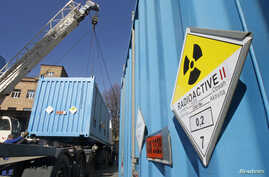 Workers place a container with spent highly-enriched uranium on a truck at a nuclear research facility in Kiev March 24, 2012…
