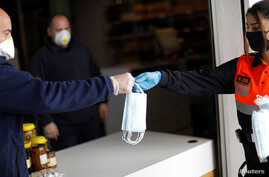 A member of Civil Protection gives out free protective face masks outside a food store during a lockdown in Spain.