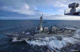 The U.S. Navy Arleigh Burke-class guided-missile destroyer USS Kidd transits alongside the aircraft carrier USS Theodore…