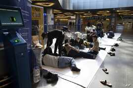 Tajikistan's people rest on the floor waiting for a plane to return in their home country at the Vnukovo international airport,…