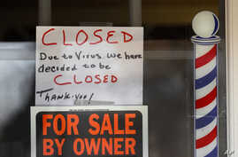 """""""For Sale By Owner"""" and """"Closed Due to Virus"""" signs are displayed in the window of Images On Mack in Grosse Pointe Woods, Mich., April 2, 2020."""